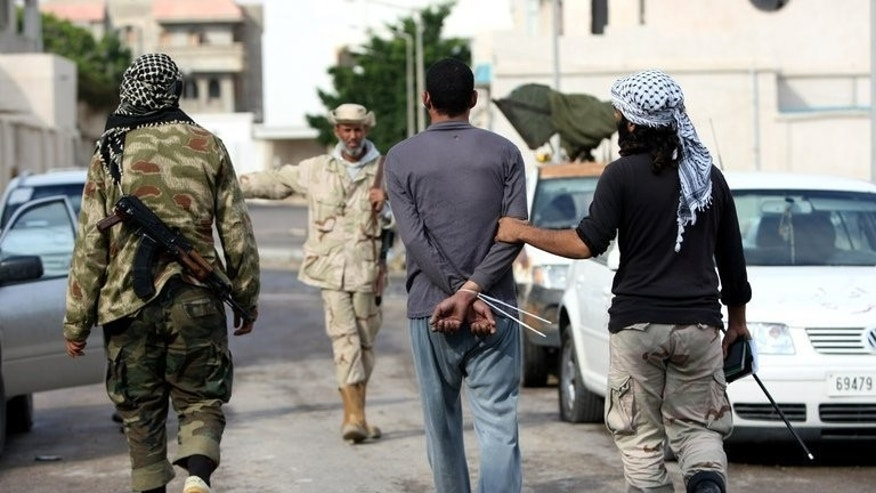 File picture shows Libyan National Transitional Council (NTC) soldiers escorting a detained fighter allegedly loyal to then dictator Moamer Kadhafi in the city of Sirte on October 13, 2011. Unknown gunmen launched a dawn attack on Tuesday on a Libyan army checkpoint south of Sirte, the home town of Kadhafi, killing six soldiers, a military officer said.
