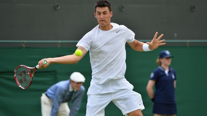Australia's Bernard Tomic hits a return against US player Sam Querrey during their men's first round match on day two of the 2013 Wimbledon Championships tennis tournament at the All England Club in Wimbledon, southwest London, on June 25, 2013. Tomic blasted the ban on his father watching him at Wimbledon, accusing the men's tour of bad manners.