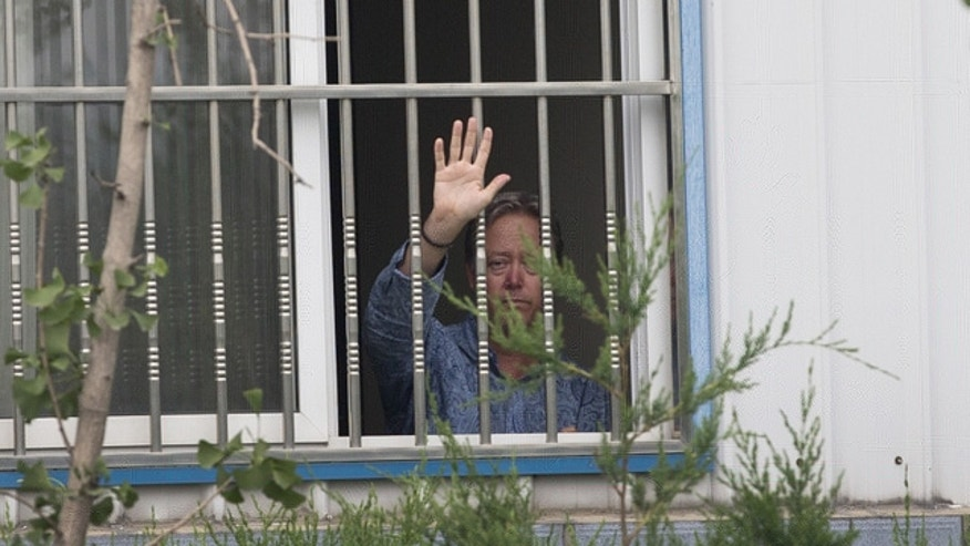 May 24, 2013: American Chip Starnes, co-owner of Specialty Medical Supplies waves from a window after he held hostage by workers inside the Specialty Medical Supplies plant at the Jinyurui Science and Technology Park in Qiao Zi township of Huairou District, on the outskirts of Beijing.