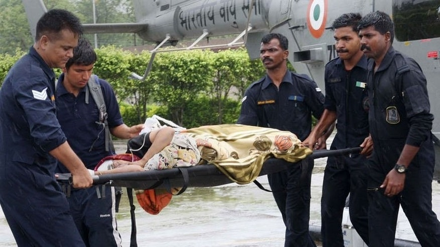 In this handout photograph received from the Ministry of Defence (MOD) on June 27, 2013 personnel transport a rescued person on a stretcher from a helicopter at Jolly Grant airport in Dehradun in the northern Uttarakhand state. Rescue workers stepped up the search for bodies Thursday in India's flood ravaged north and mass cremations took place as fears grew over outbreaks of disease.