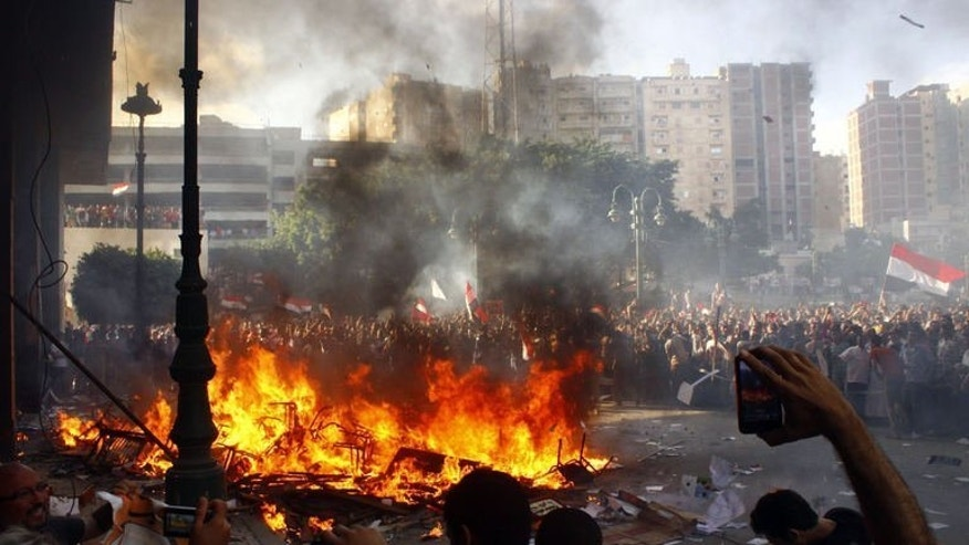 Opponents of Egyptian President Mohamed Morsi burn the contents of a Freedom and Justice Party office in the coastal city of Alexandria on June 28, 2013. An American was among three people killed in Egypt on Friday as clashes erupted during rival demonstrations for and against Morsi a year after his election