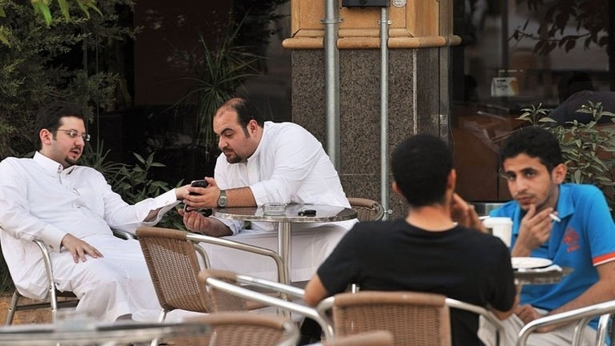 Men look at a mobile as they sit in a coffee shop in the Saudi capital Riyadh on June 17, 2013. In the United Arab Emirates and all across the conservative Gulf countries dating is unacceptable while arranged marriages are the norm, so to beat the segregation imposed by a stern society, young men and women meet virtually.
