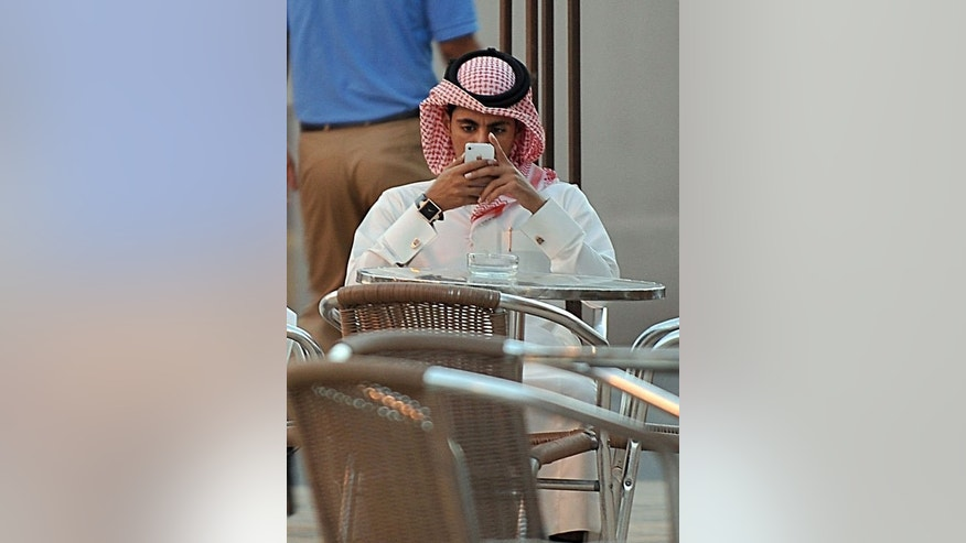 A man checks his mobile at a coffee shop in the Saudi capital Riyadh on June 17, 2013. In the United Arab Emirates and all across the conservative Gulf countries dating is unacceptable while arranged marriages are the norm, so to beat the segregation imposed by a stern society, young men and women meet virtually.