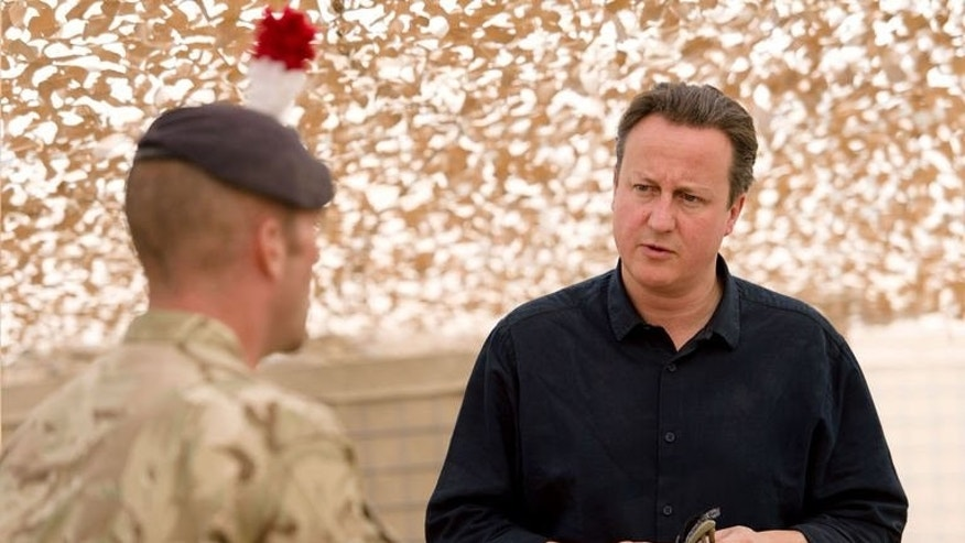 British Prime Minister David Cameron is shown a map of the area by Major Jim Skelton during a visit to Camp Bastion in Afghanistan's southern Helmand province, on June 29, 2013. Cameron made an unannounced visit to Afghanistan, backing talks with the Taliban as his top general said the West missed a chance to strike a peace deal 10 years ago.