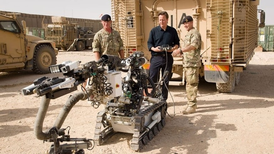 British Prime Minister David Cameron is shown a remote-controlled IED detection unit used in regional operations during a visit to Camp Bastion in the southern Helmand province, on June 29, 2013. Cameron made an unannounced visit to Afghanistan visiting troops in Helmand as the NATO military coalition hands responsibility over to local forces.