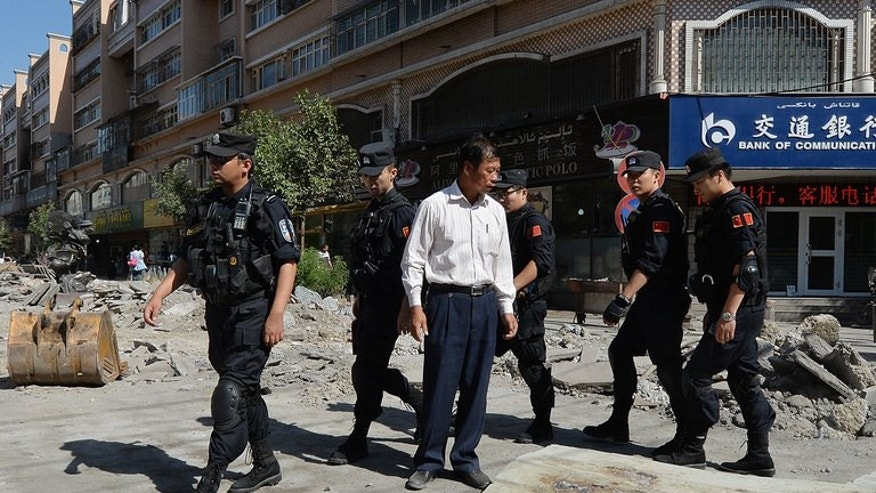 """Chinese armed police patrol the streets of the Muslim Uighur quarter in Urumqi on Saturday. China's state-run media on Saturday blamed over 100 people it branded """"terrorists"""" for sparking """"riots"""" in the ethnically-divided region of Xinjiang, where days earlier clashes killed 35."""