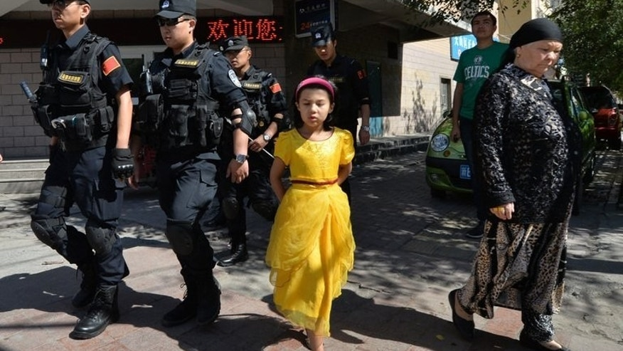 """Chinese armed police patrol the streets of the Muslim Uighur quarter in Urumqi on June 29, 2013. China's state-run media blamed about 100 people it branded """"terrorists"""" for sparking """"riots"""" in the ethnically divided region of Xinjiang, where earlier clashes killed 35."""