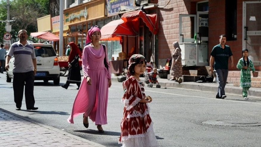 """People near the main bazaar in the Muslim quarter of Urumqi, Xinjiang Province on Saturday. Radio Free Asia, which is funded by the US government, quoted a resident as saying that local Uighurs were angry police had """"stormed into the mosque and surrounded it"""" during prayers last week because the local imam had deviated from an officially sanctioned sermon."""