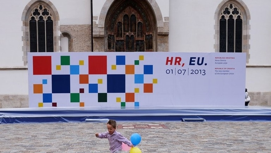 A child runs past a billboard marking Croatia's entry into the European Union, June 28, 2013, in Saint Mark's square in downtown Zagreb. Croatia on Sunday stages celebrations to mark its historic entry into the European Union as the bloc's 28th member, almost two decades after the end of the Balkan state's bloody war of independence from the former Yugoslavia.