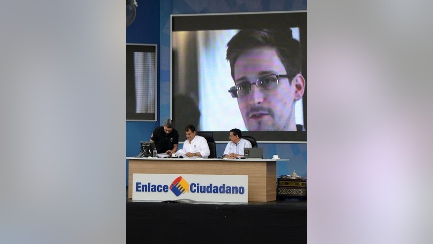 Ecuadoran President Rafael Correa holds his weekly address in front of an image of Edward Snowden in El Aromo, Manabi, on June 29, 2013. Correa, who earlier this week said he had yet to consider letting US intelligence leaker Snowden enter his country, said he spoke about Snowden with US Vice President Joe Biden.