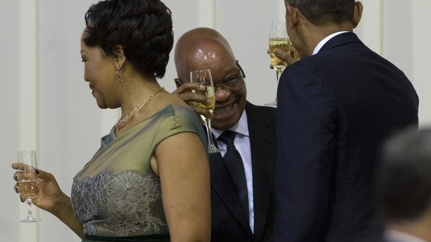 South African President Jacob Zuma and US President Barack Obama toast each other alongside Zuma's wife, Thobeka Zuma, during an official dinner at the Presidential Guest House in Pretoria, June 29, 2013. Obama will Sunday stare into the cell where Nelson Mandela spent years as prisoner, in a visit paying homage to his hero after he left Johannesburg without seeing the ailing icon.