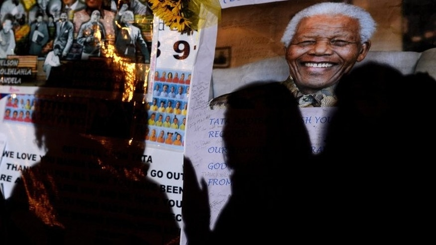 People stand vigil in front of a portrait of Nelson Mandela outside the Mediclinic Heart hospital where the former South African president is hospitalized on June 29, 2013 in Pretoria. President Barack Obama will Sunday visit the cell where Mandela spent years as prisoner of a racist regime, in a visit paying homage to his hero after he left Johannesburg without seeing the ailing icon.