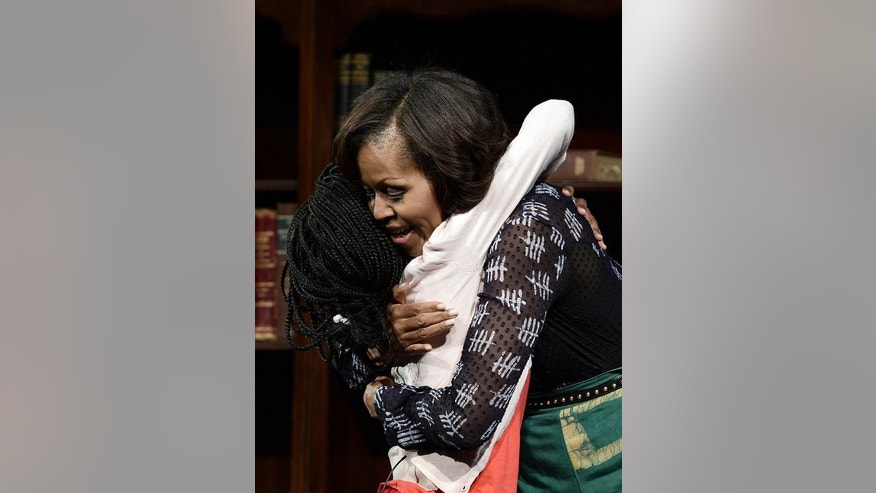 US First Lady Michelle Obama hugs a student during a discussion on June 29, 2013 at the Sci-Bono Discovery Center in Johannesburg. The first lady was joined by teenagers from across South Africa as well as students joining virtually from cities around the US.