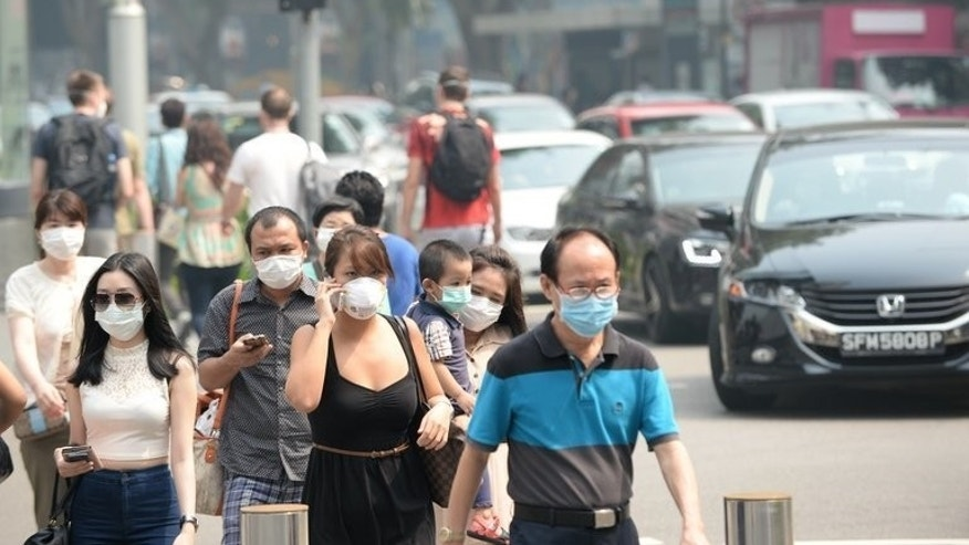 People wear face masks on Orchard Road in Singapore last week. The foreign ministers of Singapore, Malaysia and Indonesia met Saturday to discuss solutions to the choking smog coming from forest fires in Sumatra ahead of a regional security forum.