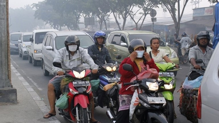 Riders wear masks on a road in Pekabaru, Indonesia's Riau province on Sumatra island last week. Haze is an annual problem during the dry season but this year's outbreak has been the worst in years, raising temperatures between Indonesia and its neighbours.