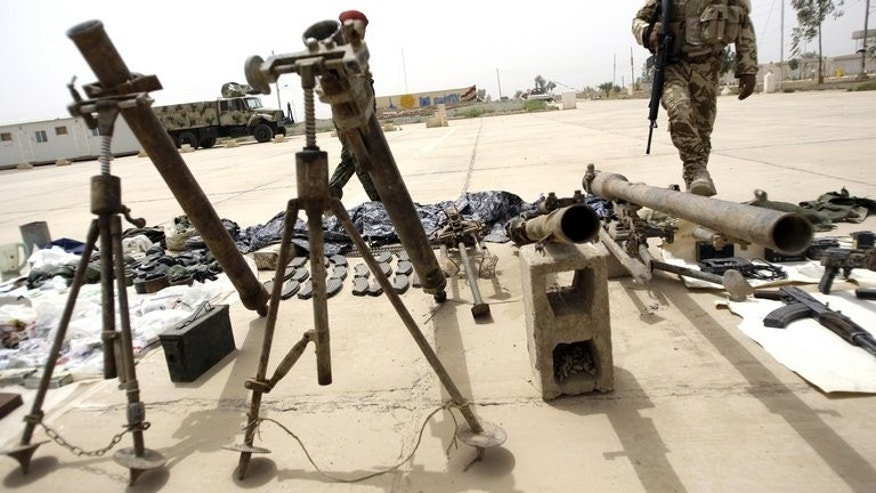 A soldier at an Iraqi base in Abu Ghraib in May 2010 guards weapons seized by security forces. In Abu Ghraib, just west of Baghdad, a bomb in a market on Saturday killed three people and wounded at least 10 others.