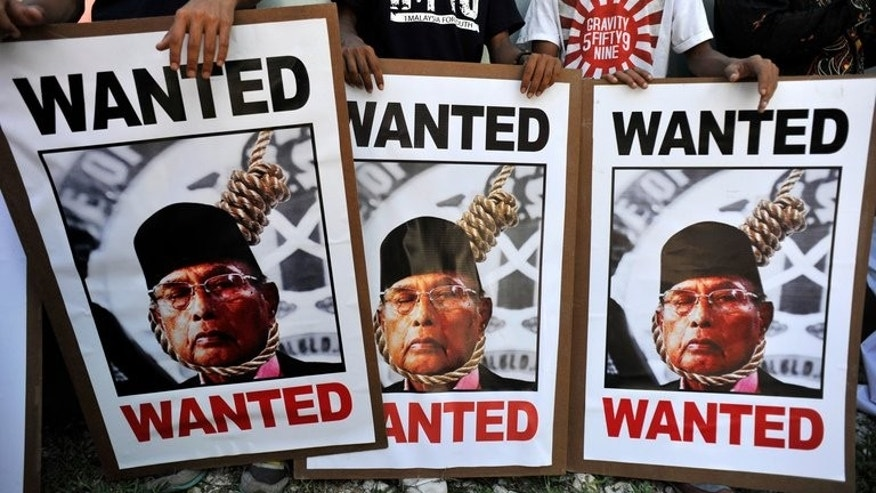 Protesters display posters of Sultan Jamalul Kiram III at the Philippines embassy in Kuala Lumpur in March. Malaysian authorities Saturday announced that an operation to flush out armed Filipino militants from an eastern state was over, four months after the intruders landed on Borneo island sparking a security crisis.