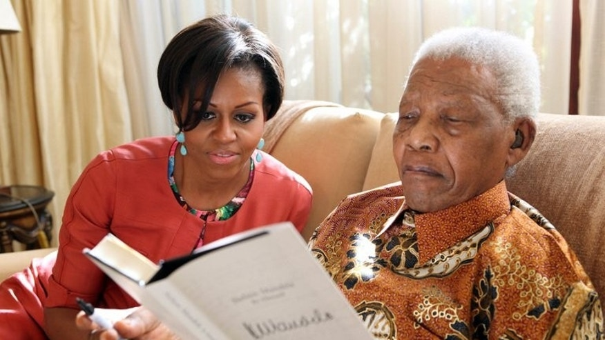 "Nelson Mandela with Michelle Obama at Mandela's home in Johannesburg in 2011. US President Barack Obama on Saturday hailed the ""moral courage"" of Nelson Mandela, which he said was an inspiration to the world."