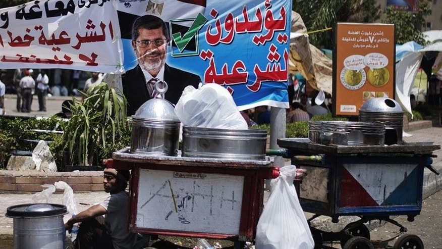 A street vendor sits by his cart as supporters of Egyptian President Mohamed Morsi and the Muslim Brotherhood camp outside the Rabaa al-Adawiya mosque in Cairo on June 29, 2013. Egypt braced for mass protests Sunday with Morsi's opponents determined to oust him and his Islamist supporters vowing to defend his legitimacy to the end, on the anniversary of his turbulent first year in office