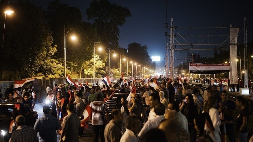 Hundreds of Egyptian protesters wave national flags and shout slogans against President Mohammed Morsi outside the presidential palace on June 29, 2013 in Cairo. Egypt braced for mass protests Sunday with Morsi's opponents determined to oust him and his Islamist supporters vowing to defend his legitimacy to the end, on the anniversary of his turbulent first year in office