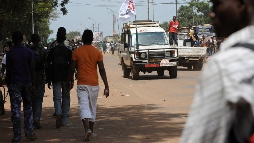 People walk past a car with a flag of Medecins Sans Frontieres (MSF, Doctors without borders) in a street of Bangui, on March 28, 2013.