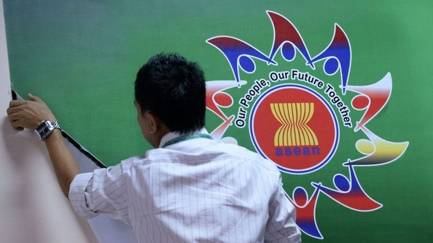 A man adjusts a banner for the ASEAN foreign ministers' meeting in Bandar Seri Begawan on June 29, 2013. Southeast Asia's top diplomats were set to kick off the major regional forum on Sunday with a firm focus on trying to ease tensions with China over a territorial row, amid warnings that failure could lead to conflict.