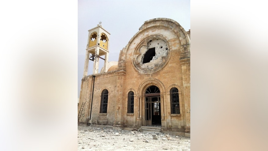 The damaged Saint Elias church in Qusayr in Syria's central Homs province earlier this month. War planes have carried out two consecutive raids against areas under siege in Homs city, as well as carrying out heavy shelling against the same districts, the Syrian Observatory for Human Rights says.