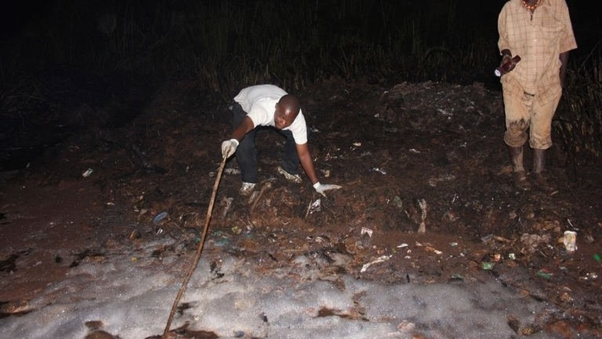 A man uses a stick to as he tries to pull out a body from a hole on June 30, 2013 in Namungoona, a Kampala suburb. At least 31 people have died in a blaze that engulfed an oil tanker after it was hit by another vehicle in a suburb of the Ugandan capital, police said Sunday.