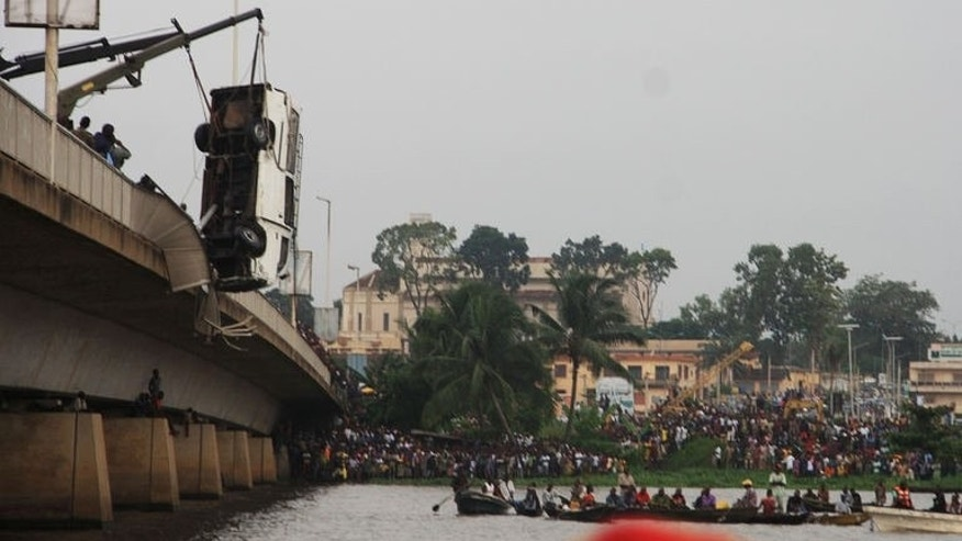 A crane retrieves a minibus from a river after it careered off a bridge just outside of Benin's capital Porto-Novo on June 30, 2013.