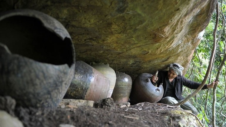 Cambodian archaeologist Tep Sokha studies bone from a jar in a cave at Phnom Pel, southwest of Phnom Penh, on March 24, 2013. Ten jars, dating from the 15th to the 17th centuries, and twelve coffins -- the earliest from the 14th century -- have been found at the site.