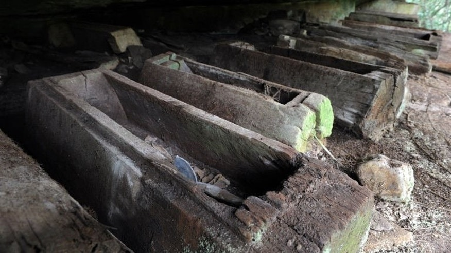 This photo taken on March 24, 2013 shows coffins in a cave at Phnom Pel, Cambodia. Over a hundred 'burial jars' and a dozen coffins have for centuries held the bones -- and secrets -- of a mysterious people who lived alongside with the Angkor era.
