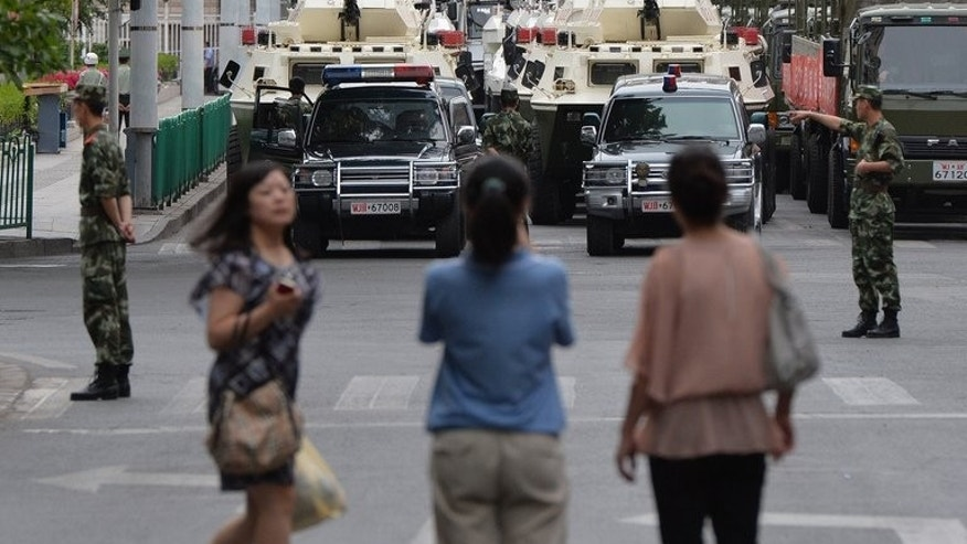 People watch as paramilitary police and armoured vehicles parade in Urumqi on June 29, 2013. The exercises saw large sections of the city shut down as military vehicles took to the streets with at least 1,000 personnel from the People's Armed Police.