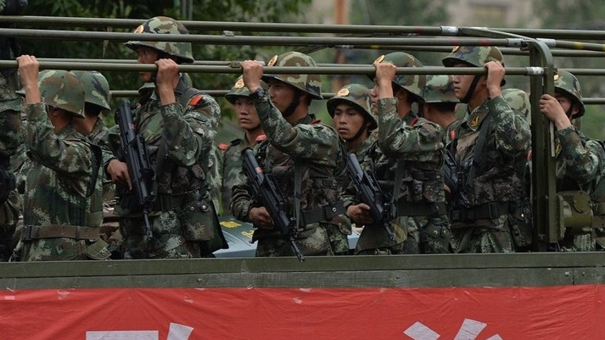 "Chinese paramilitary police armed with assault rifles ride in trucks during a show of force in Urumqi on June 29, 2013. China has vowed to ramp up patrols and ""crack down upon terrorist groups"" in the ethnically divided Xinjiang region."