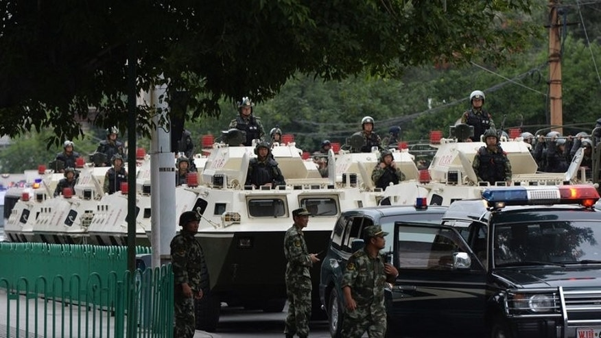 "Chinese paramilitary police prepare to ride in armoured vehicles, in Urumqi, on June 29, 2013. The state run Global Times newspaper Sunday described the exercises as ""ceremonies... to support the fight against terrorism""."