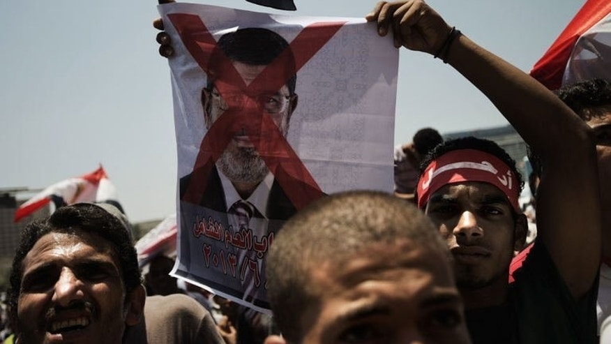An Egyptian opposition supporter holds a crossed-out picture of President Mohammed Morsi in Cairo's landmark Tahrir Square on June 29, 2013.