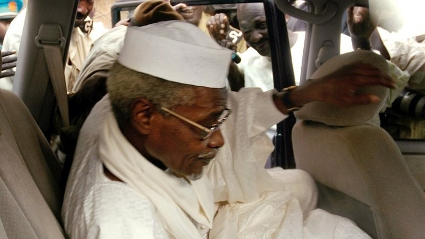 "Chad's ex-dictator Hissene Habre leaves Dakar's courthouse escorted by prison guards, November 25, 2005. Habre, detained by Senegal on Sunday in the first step towards a trial for war crimes, is known as ""Africa's Pinochet"" for his eight-year rule over Chad which began and ended in violence."