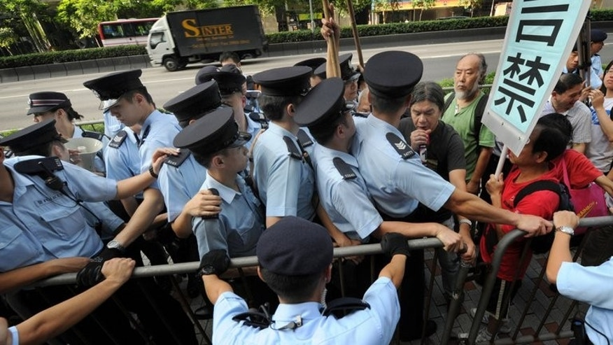 A small group of protestors are blocked by dozens of police as they attempt to march in Hong Kong on July 1, 2010. Huge crowds will march through Hong Kong Monday to protest against the city's pro-Beijing leader and the pace of political reforms, as the former British colony marks the 16th anniversary of its handover to China.