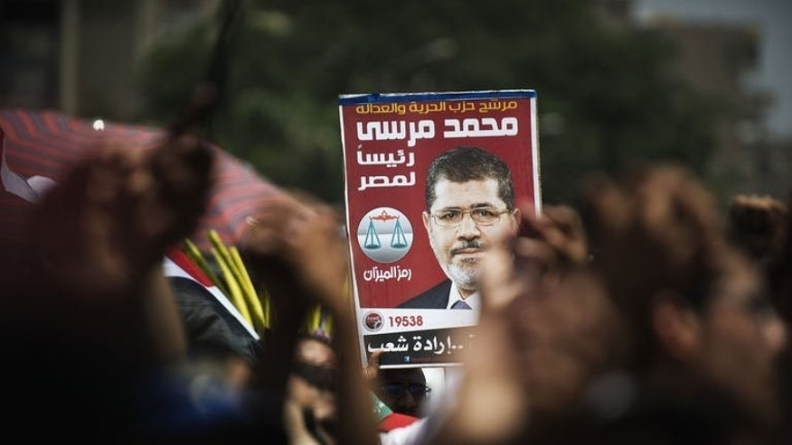 "Supporters of Egyptian President Mohamed Morsi hold his poster outside the Rabaa al-Adawiya mosque in Cairo on June 29, 2013. Morsi, an Islamist who pledged to be a ""president for all Egyptians"" at his inauguration, faces mass rallies demanding his departure on the first anniversary of his taking office."