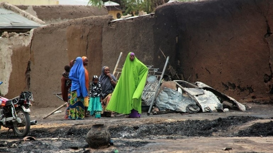 "Nigeria women and children allegedly ousted from their homes by soldiers stand in front of burnt houses in Baga town on April 21, 2013. Soldiers fired wildly ""at anybody in sight"" during a deadly April incident in the town, a police report cited by the country's Human Rights Commission said."