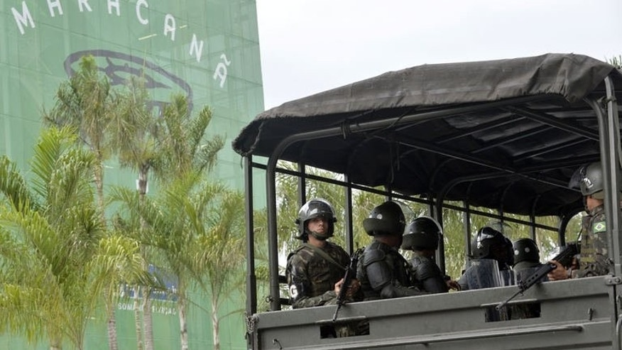 A truck carrying soldiers drive by the Maracana stadium of Rio de Janeiro on June 30, 2013.
