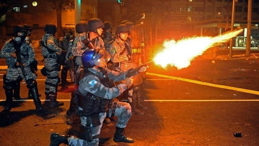Riot squad officers clash with protestors on a street near Maracana stadium in Rio de Janeiro, Brazil on June 30, 2013. Protesters armed with screwdrivers and slingshots clashed with police near Rio's legendary Maracana football stadium where Brazil defeated Spain to win a third successive Confederations Cup.