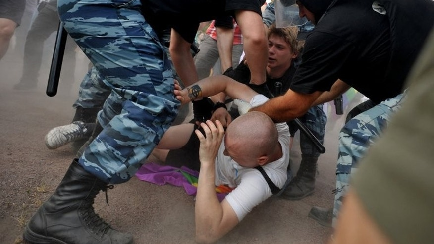 "Russian riot police detain anti-gay protesters during a gay pride event in St. Petersburg on Saturday. The anti-propaganda law introduces fines of up to 5,000 rubles ($156) for citizens who disseminate information aimed at minors ""directed at forming nontraditional sexual setup"" or which may cause a ""distorted understanding"" that gay and heterosexual relations are ""socially equivalent""."