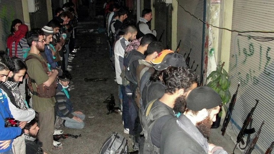 "Rebel fighters praying in Syria's central city of Homs on June 17. Syria's Al Watan daily, which is close to the government, said on Sunday that the army had ""made qualitative new advances in the city of Homs amid fierce clashes with armed militias in Khalidiyeh and Bab Hud."""