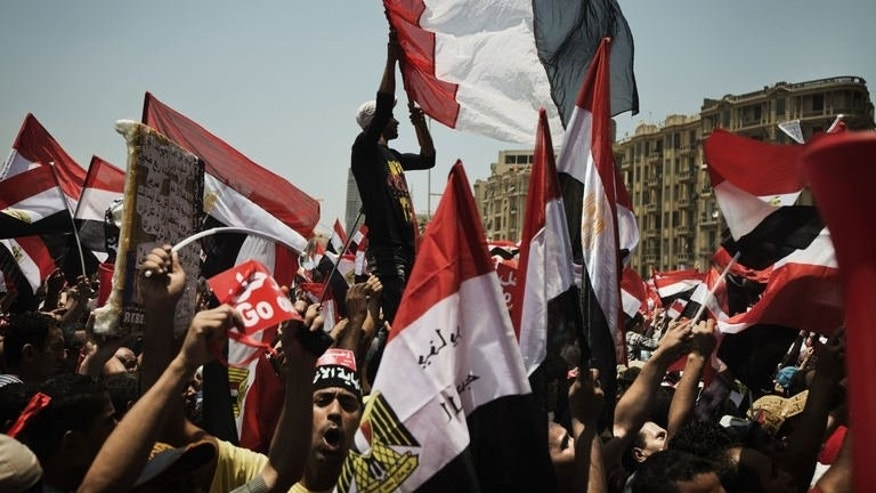 Egyptians wave their national flag as they protest against the country's President Mohamed Morsi and the Muslim Brotherhood in Cairo's landmark Tahrir square on June 30, 2013.
