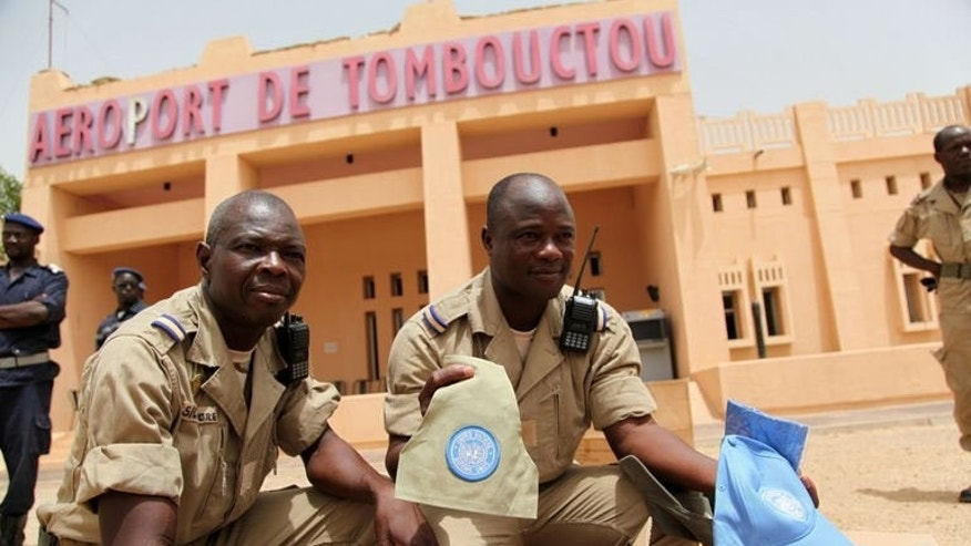 Soldiers hold up UN caps and insignia outside the airport of Timbuktu on June 30, 2013. A 12,600-strong force will take over security duties from French troops who entered Mali in January to halt an Islamist advance and help the government re-establish its authority over the vast country.