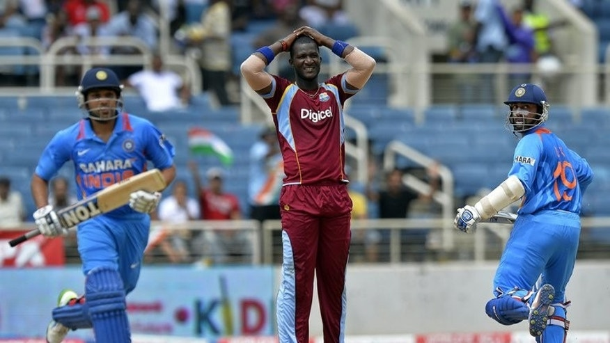 Dinesh Karthik (right) and Rohit Sharma take a run off the bowling of Darren Sammy (centre) in Kingston on Sunday. Stand-in West Indies captain Kieron Pollard won the toss and put India in to bat in the second match of the Tri-Nation One-Day International Series at Sabina Park.