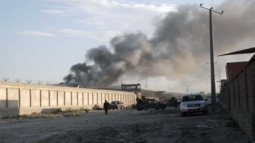 July 2, 2013: Smoke rises from a NATO compound following a suicide bombing in Kabul, Afghanistan. Militants blew up a suicide car bomb at the gate to the NATO compound in Kabul early Tuesday and attacked guards with small-arms fire, killing four guards and two civilians, police said. All four suicide attackers were also killed.