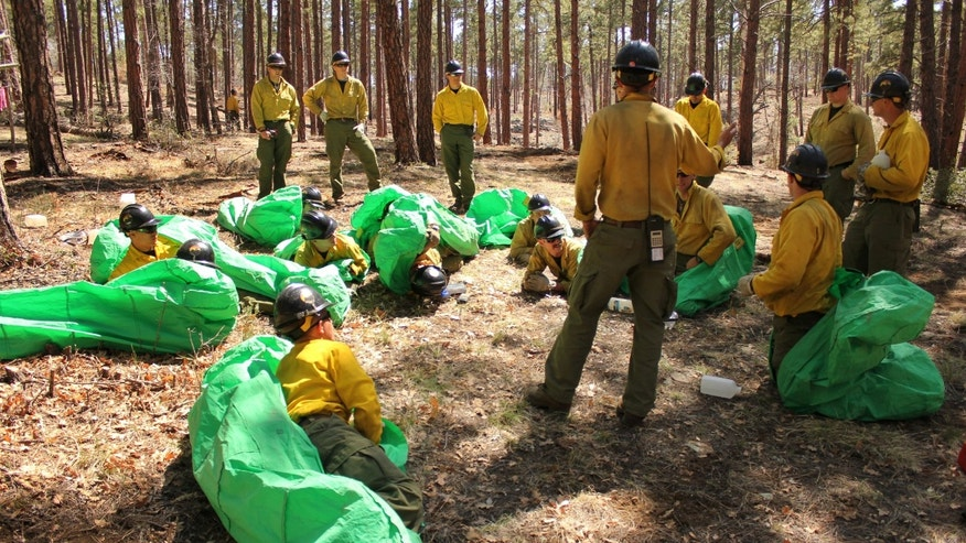 In this April 12, 2012 photo provided by the Cronkite News, Phillip Maldonado, a squad leader with the Granite Mountain Hotshots, trains crew members on setting up emergency fire shelters outside of Prescott, Ariz.
