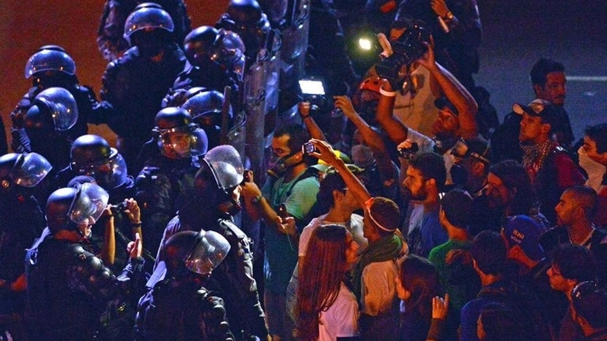 Protestors face riot squad officers on a street near Maracana stadium in Rio de Janeiro, Brazil on June 30, 2013, a few hours before the final of the FIFA Confederations Cup football tournament between Brazil and Spain.