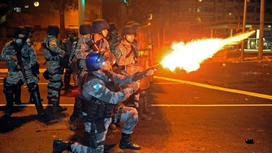 Riot squad officers clash with protestors on a street near Maracana stadium in Rio de Janeiro, Brazil on June 30, 2013, a few hours before the final of the FIFA Confederations Cup football tournament between Brazil and Spain.